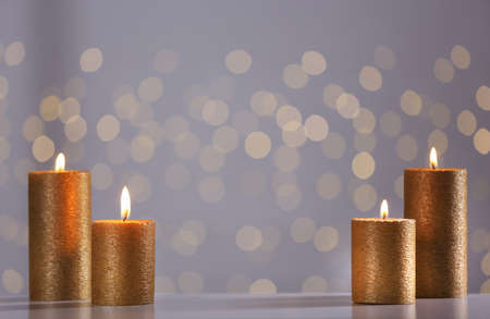Burning gold candles on table against blurred lights. Space for text Archivio Fotografico