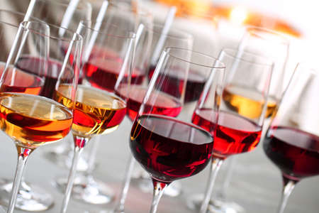 Glasses with different wines on blurred background, closeup