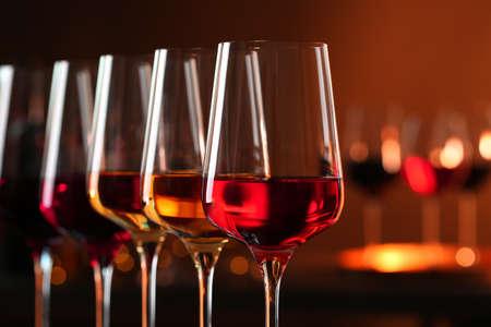 Fila de vasos con diferentes vinos contra el fondo borroso, primer plano. Espacio para texto Foto de archivo