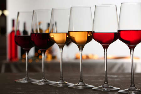 Row of glasses with different wines on table against blurred background