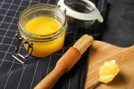 Composition with clarified butter and basting brush on table Stock Photo
