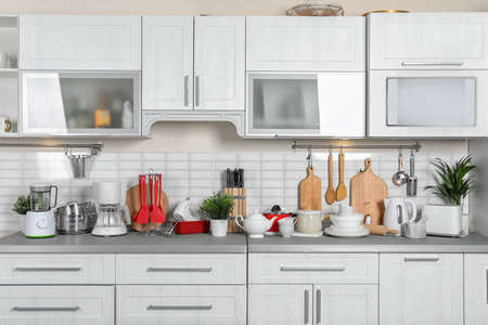 Kitchen interior with clean dishes, cookware and appliances