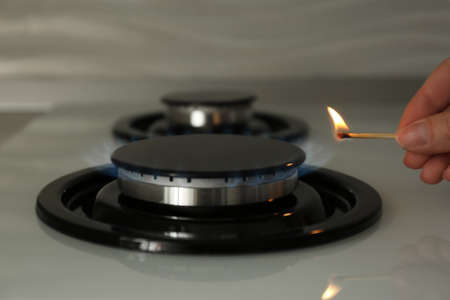 Woman lighting gas stove with match, closeup