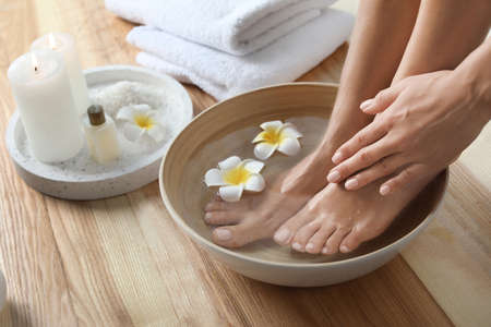 Closeup view of woman soaking her feet in dish with water and flowers on wooden floor. Spa treatment