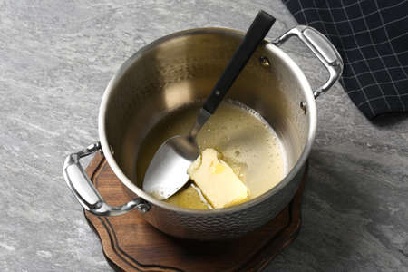 Pot with melting butter and spoon on grey table