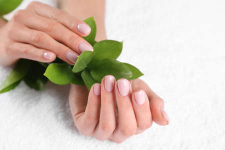 Closeup view of beautiful female hands with green leaves on towel, space for text. Spa treatment