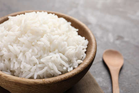 Bowl of tasty cooked rice served on table, closeup. Space for text