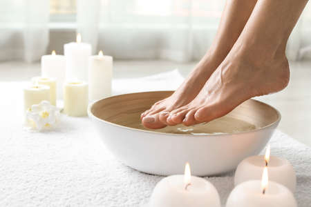 Woman soaking her feet in dish indoors, closeup with space for text. Spa treatment Banque d'images