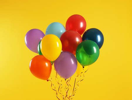 Montón de globos brillantes sobre fondo de color. Hora de celebrar
