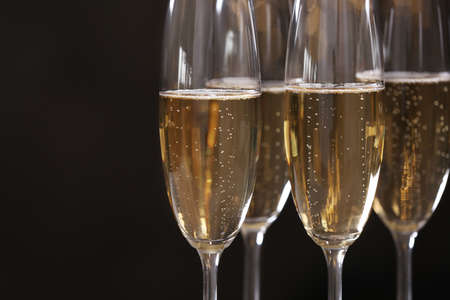 Glasses of champagne on dark background, closeup. Space for text