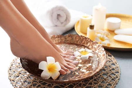 Acercamiento de la mujer remojando sus pies en un plato con agua y flores en el piso gris. tratamiento de spa