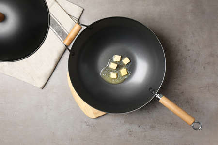 Flat lay composition of frying pan with melting butter on grey table