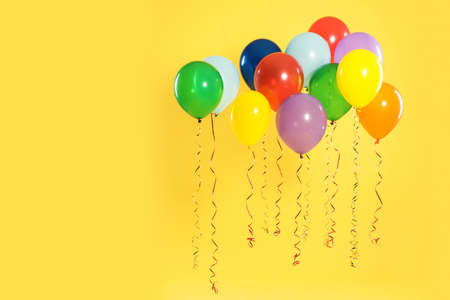 Bright balloons on color background, space for text. Celebration time