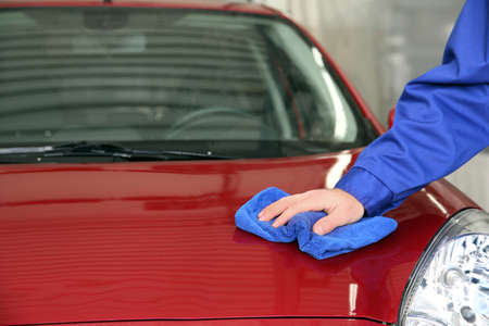 Worker cleaning automobile bonnet with rag at car wash, closeup Stockfoto