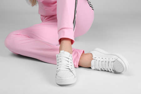 Woman in stylish sport shoes sitting on light background Stockfoto
