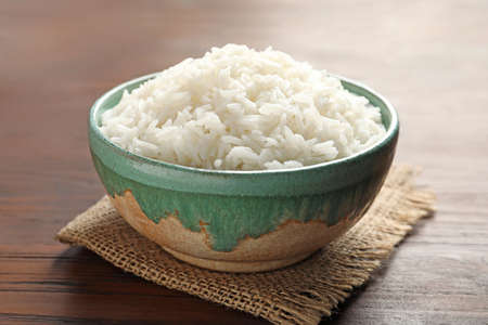 Bowl of tasty cooked white rice on wooden table, closeup Reklamní fotografie