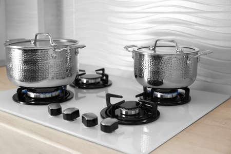 Shiny steel saucepans on modern gas stove
