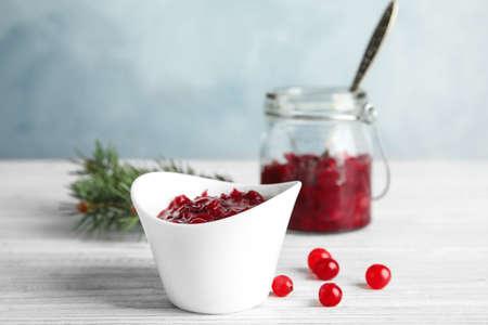 Bowl of tasty cranberry sauce on table Zdjęcie Seryjne
