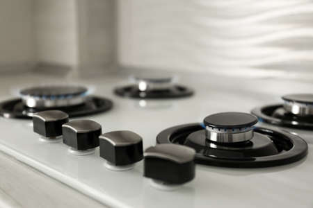 Gas burners with blue flame on modern stove, closeup