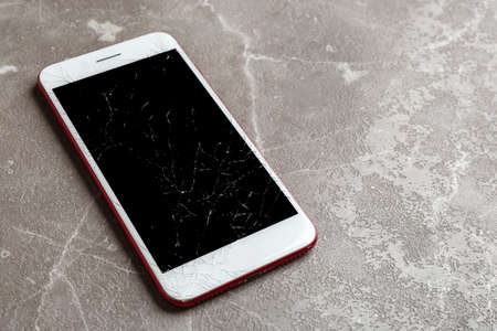 Modern smartphone with broken display on table, space for text. Device repair service Imagens