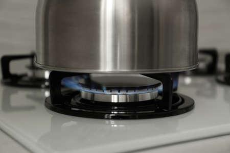 Steel kettle on modern gas stove, closeup