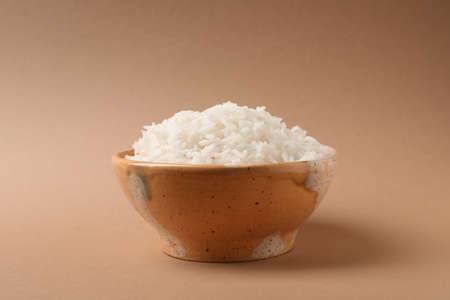 Bowl of tasty cooked rice on color background Reklamní fotografie