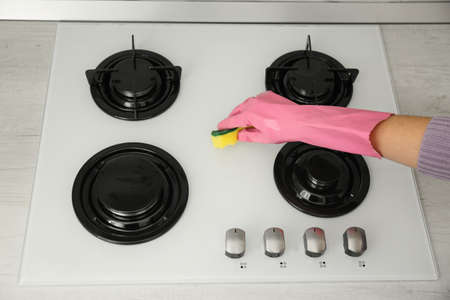 Woman cleaning gas stove with sponge, closeup