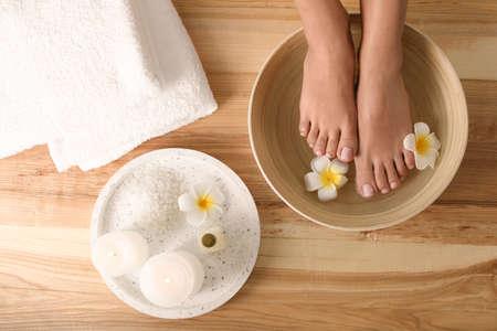 Vrouw haar voeten onderdompelen in schotel met water en bloemen op houten vloer, bovenaanzicht. Spa behandeling