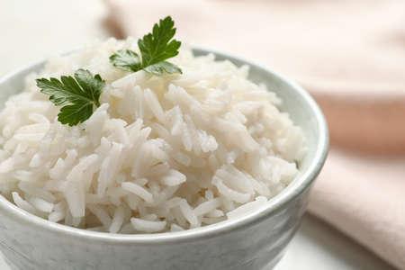 Schüssel mit leckerem gekochtem Reis mit Petersilie auf dem Tisch, Nahaufnahme