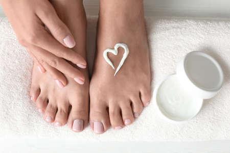 Mujer aplicando crema para pies sobre una toalla blanca, vista superior. tratamiento de spa