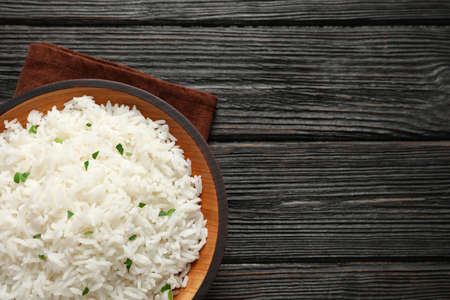 Plate of tasty cooked rice on wooden background, top view. Space for text Reklamní fotografie