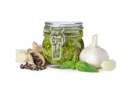 Composition with jar of tasty pesto sauce isolated on white