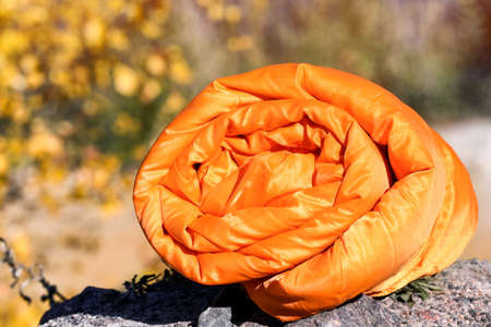 Orange sleeping bag on blurred background. Camping equipment