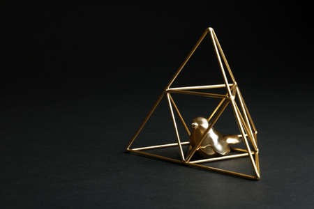 Decorative bird in gold pyramid on black background. Space for text