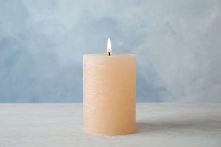 Burning candle on table against color background