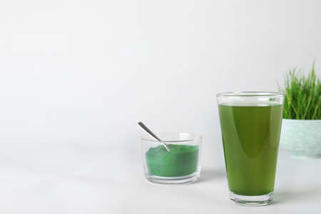 Glass of spirulina drink and bowl with powder on white background. Space for text
