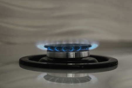 Gas burner with blue flame on modern stove, closeup. Space for text