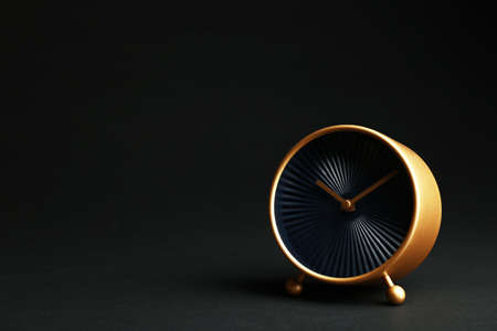 Golden alarm clock on black background. Space for text