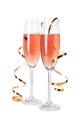 Glasses of rose champagne with gold streamer isolated on white 스톡 콘텐츠