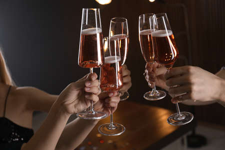 Friends clinking glasses with champagne on blurred background, closeup
