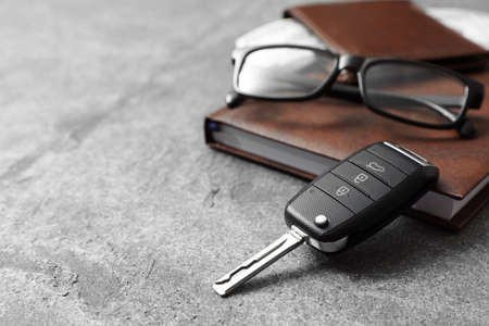 Composition with male accessories and car key on grey background. Space for text Banco de Imagens