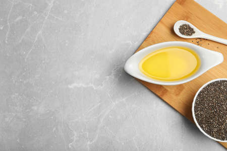 Composition with chia seeds and sauce boat of oil on grey table, top view. Space for text