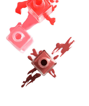 Spilled different nail polishes with bottles on white background, top view
