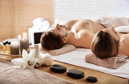 Giovane coppia con gli elementi essenziali della spa nel centro benessere