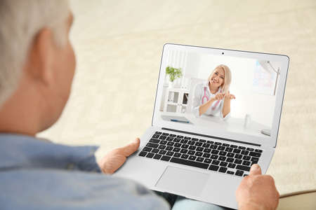 Man using laptop for online consultation with doctor via video chat at home, closeup Standard-Bild