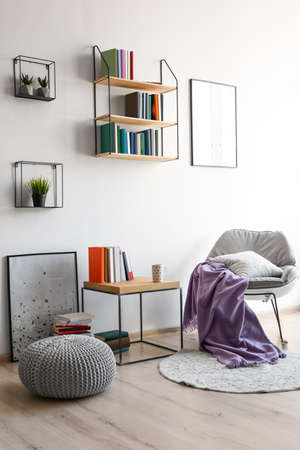 Comfortable armchair and different books near wall in room