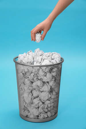 Woman throwing crumpled paper into metal bin on color background, closeup