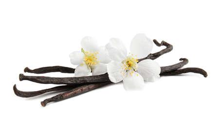 Palitos de vainilla aromáticos y flores sobre fondo blanco.