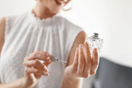 Young woman applying perfume on wrist against blurred background, closeup