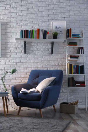 Room interior with comfortable armchair and different books near brick wall